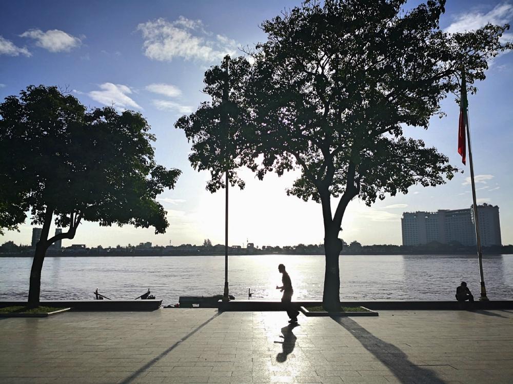 Persone che corrono sul lungofiume di Phnom Penh in Cambogia all'alba